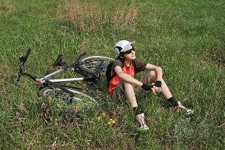 Boy sitting in field with bicycle