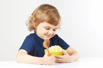 Beautiful child hugging a green bowl of millet cereal favorite