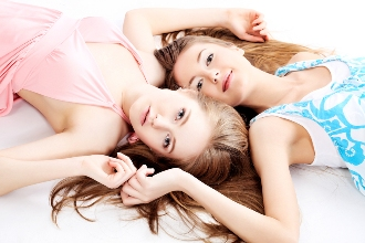 Two pretty girls lying on white floor