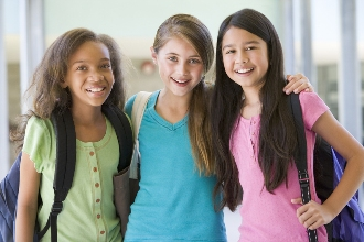 Three happy, well-adjusted tween girls standing together