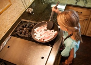 girl frying bacon in pan