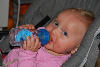 baby with bottle in car seat