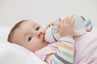 infant girl drinks milk from a bottle