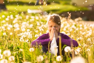 girl with hay fever in field