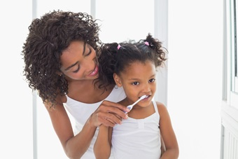 Mom helps daughter brush teeth