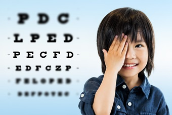 Cute asian boy doing eye test.