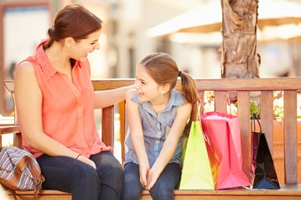 Mother And Daughter Sitting On Seat In Mall Together