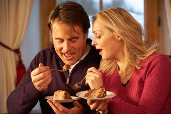 Couple Enjoying Slice Of Cake Sitting On Sofa