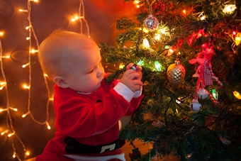 the baby around the Christmas tree playing with lights